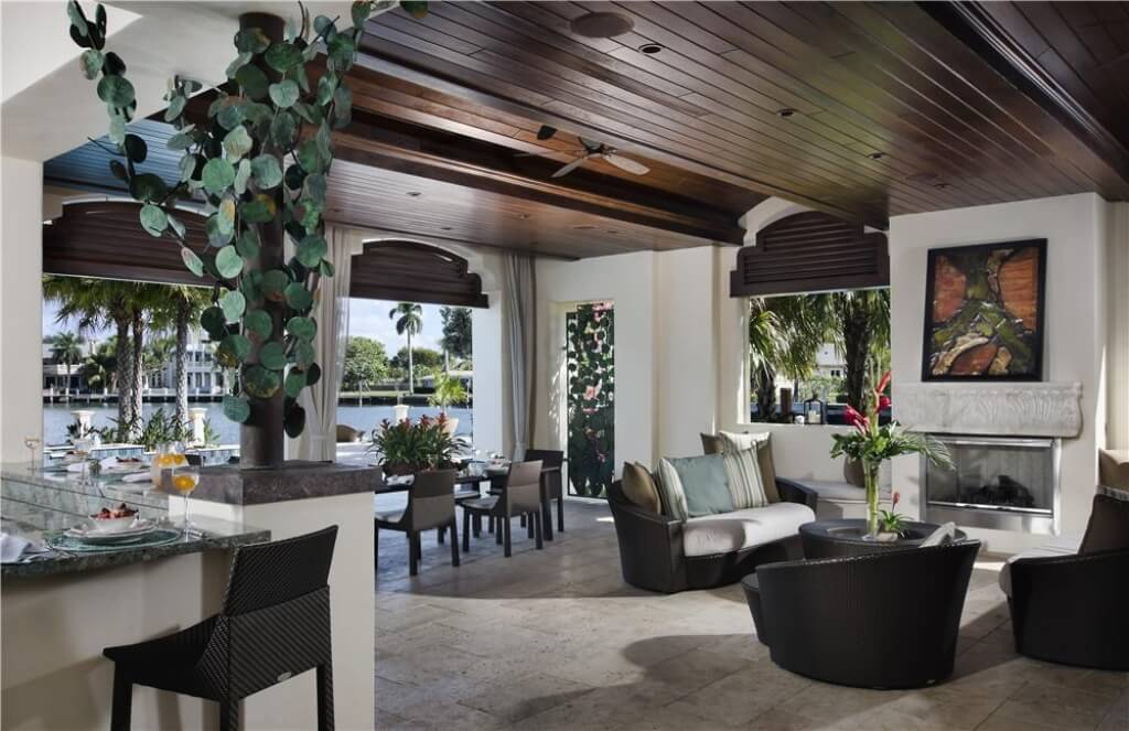 The outdoor dining area is just as expansive as the exterior, with tile floors, and high, wooden ceilings. Dark marble countertops provide contrast to the warm beige walls, which transition seamlessly into the outdoor walkways.