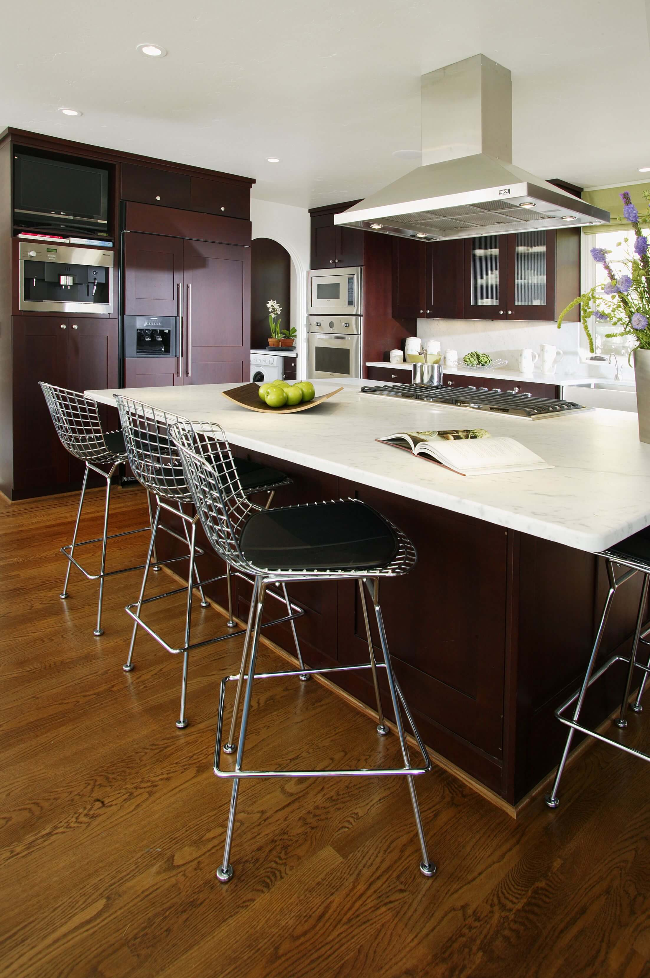 High Contrast Look In This Kitchen, Courtesy Of Dark Stained Cabinetry,  White Countertops,
