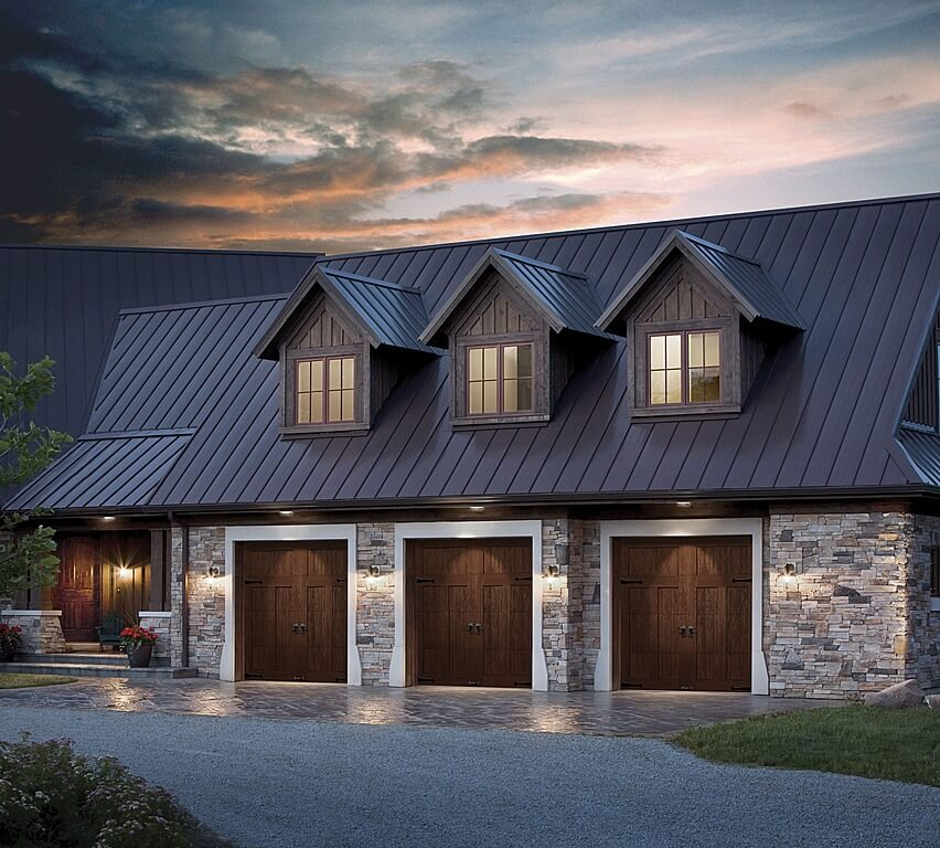 This three car garage features rich, dark wood carriage style doors framed in white, with brick stone facade.