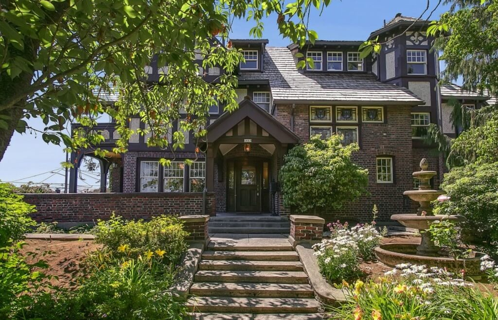 Here is the Hainsworth mansion as seen walking up the front entrance. Concrete stairs elevate to a wraparound path before reaching the brick walled patio and main entryway. Sloped garden with large fountain flanks the stairs.