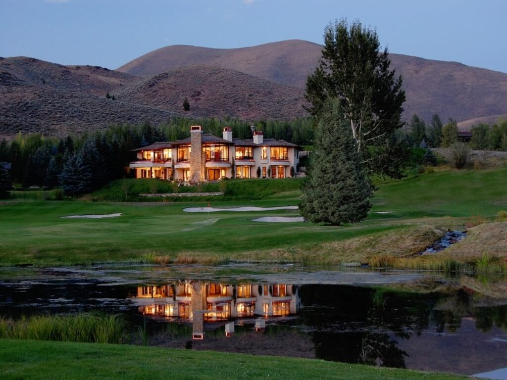 Panoramic view of Idaho mountain home and golf course at dusk.