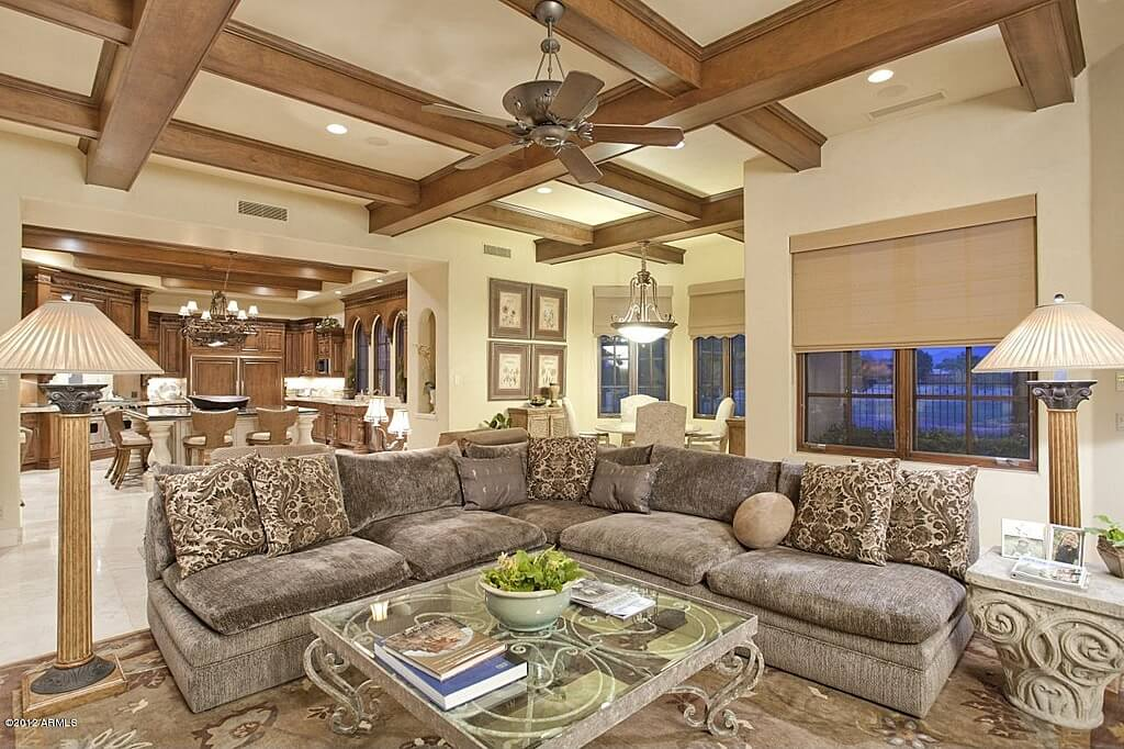 This texturally lush, open-plan living room features armless L-shaped grey sectional couch centered around ornate glass-and-metal coffee table, with exposed beams above and Greek column floor lamps flanking.
