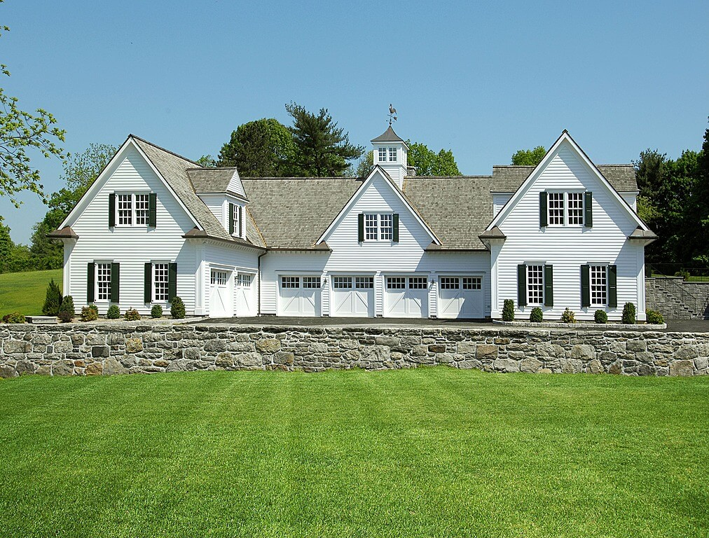 This immense carriage house in white is larger than many full homes. With stalls facing forward and inward, carriage style doors with upper panel windows abound.