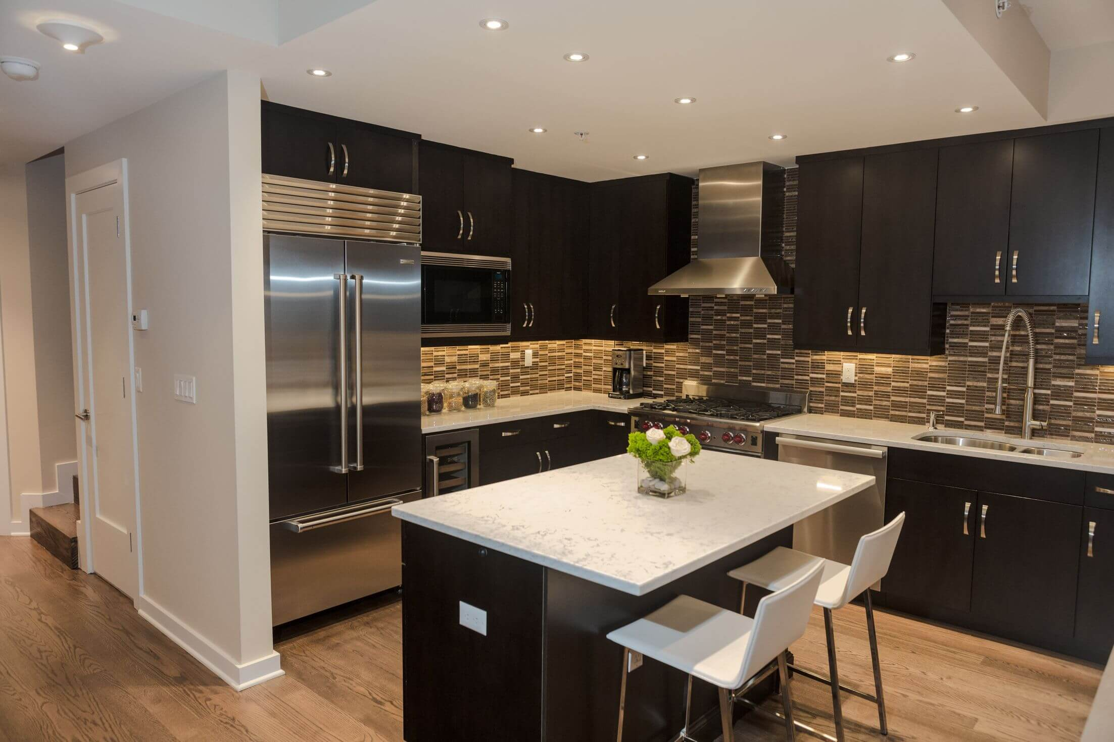 Black wood cabinetry and island contrast with patterned tile backsplash white marble countertops and