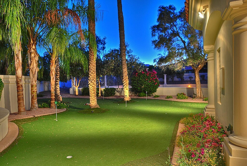 This custom green wraps around palms in this backyard featuring gentle elevation changes, for a challenging putt.