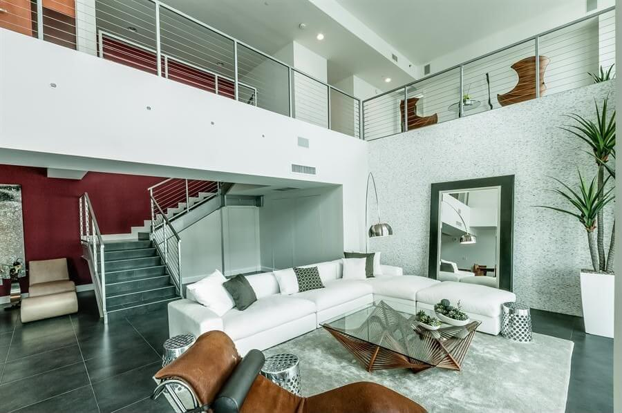 Multi-textured living room features bright white L-shaped sectional sofa on plush white rug over dark marble flooring, with second floor balcony overlook and leather chaise in foreground.