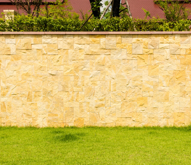 This intricate, varied brick fence design in yellow tones is topped with flat red bricks and greenery.