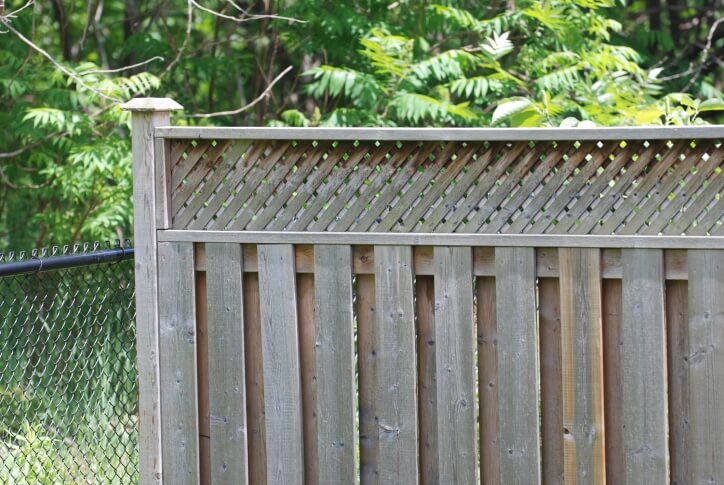 Untreated wooden fence design features layered posts with lattice style top section.