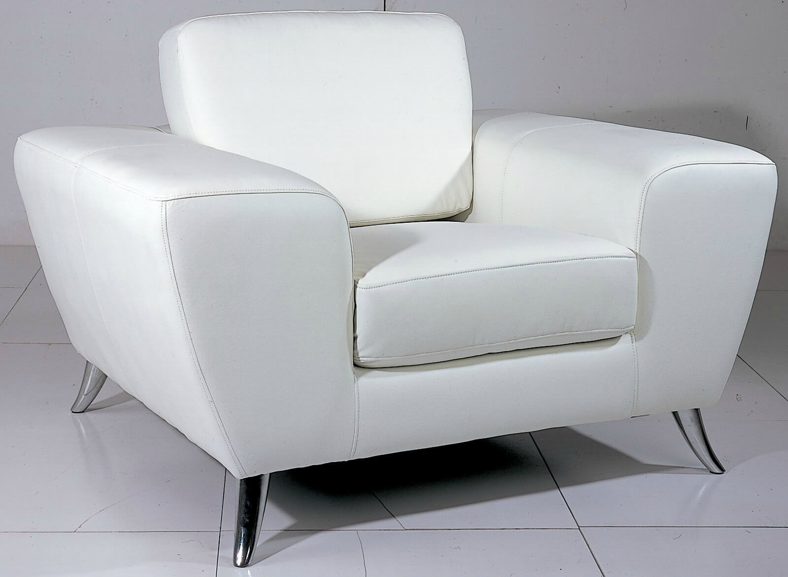 This top grain leather chair from Beverly Hills Furniture is constructed of kiln-dried hardwood with chromed metal legs, supporting polyurethane cushioning and removable back pillows in a unique, modern shape.