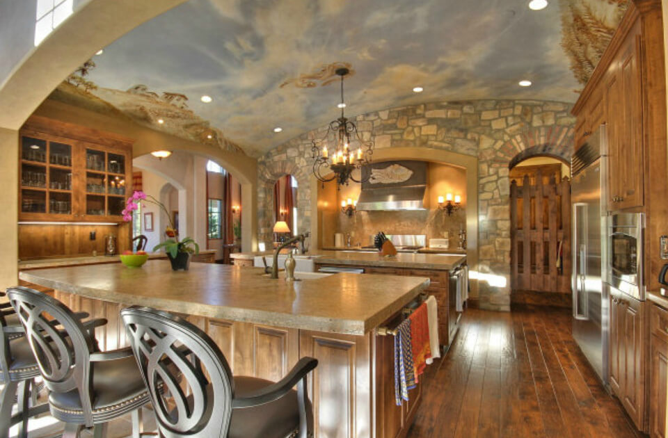 The kitchen is impressive in design featuring two islands, wood flooring, stone walls and a blue-sky mural ceiling