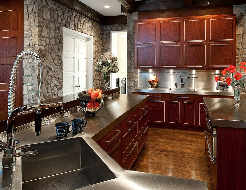 Unique metal countertops surround this kitchen, matching cabine hardware over cherry wood paneling, with dark natural wood flooring. Stone outer walls ground the look.