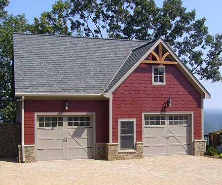 Cozy red shingle carriage house features two stalls separated by central window, with brown painted wood carriage style doors.