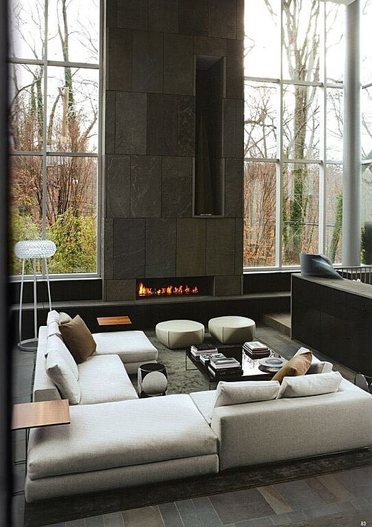 Modern, minimalist design in this tall space featuring stone fireplace surround, floor to ceiling windows, and white, U-shaped modern sectional sofa with twin round ottomans and black glass coffee table.