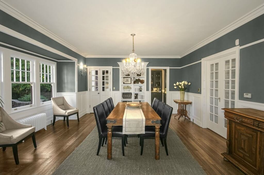 Formal dining room continues dark hardwood flooring from living room, with lengthy natural wood table and black leather seating at center. French doors to living room and patio feature, along with large wall-built white shelving at rear center.