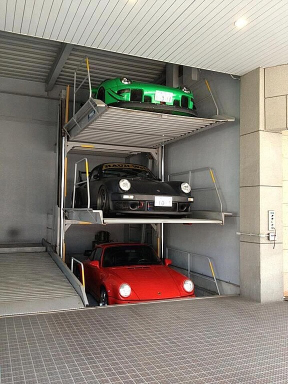 This garage features professional style lift system for storing racing Porches.