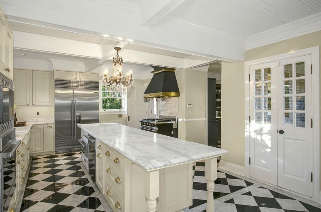 Kitchen features black and white checkered marble flooring, with large white wood island featuring expanse of marble countertop and dining space at end. French doors open to outdoors, while traditional, ornate chandelier hangs from white painted beams.