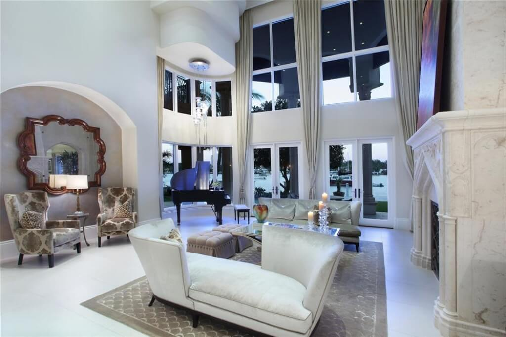 Two-story windows show off the beautiful lakefront view. A large mirror reflects the view and marble accents above the fireplace further enhance a luxurious living room.