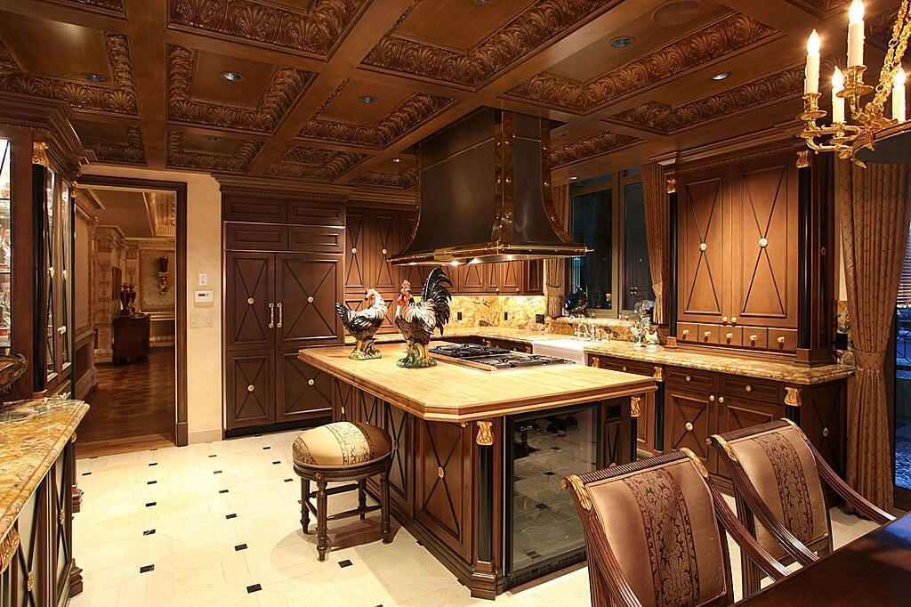 Lush Carved Wood Cabinetry Details Abound In This Kitchen Featuring Large  Natural Wood Topped Island Beneath