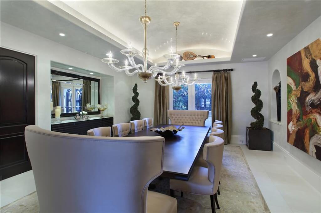 Elegant Murano glass chandeliers draw the eye through this room and to the window. A long dining table allows for comfortable seating of small or large parties.