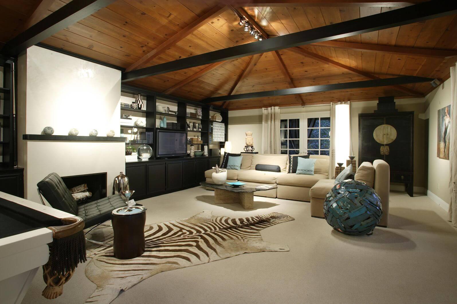 Grand salon décontracté avec un canapé et un fauteuil sans bras beiges, un fauteuil sans bras noir moderne et une large peau de zèbre sur le sol couvrant une grande partie de la pièce