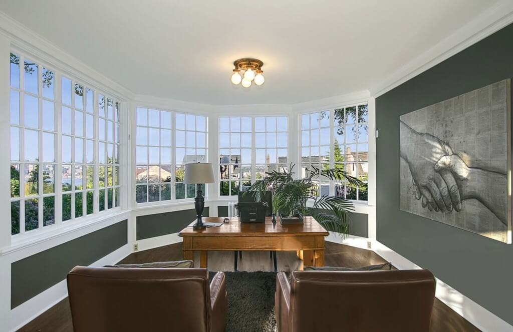 Large corner office features curved exterior wall comprised almost completely of windows. Hardwood flooring contrasts with grey walls and white trim, while large natural wood desk sits across dark shag rug from twin leather armchairs. Large painting of handshake detail adorns right wall.