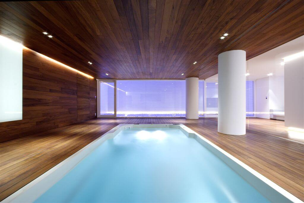 Modern indoor pool opening to outdoor patio