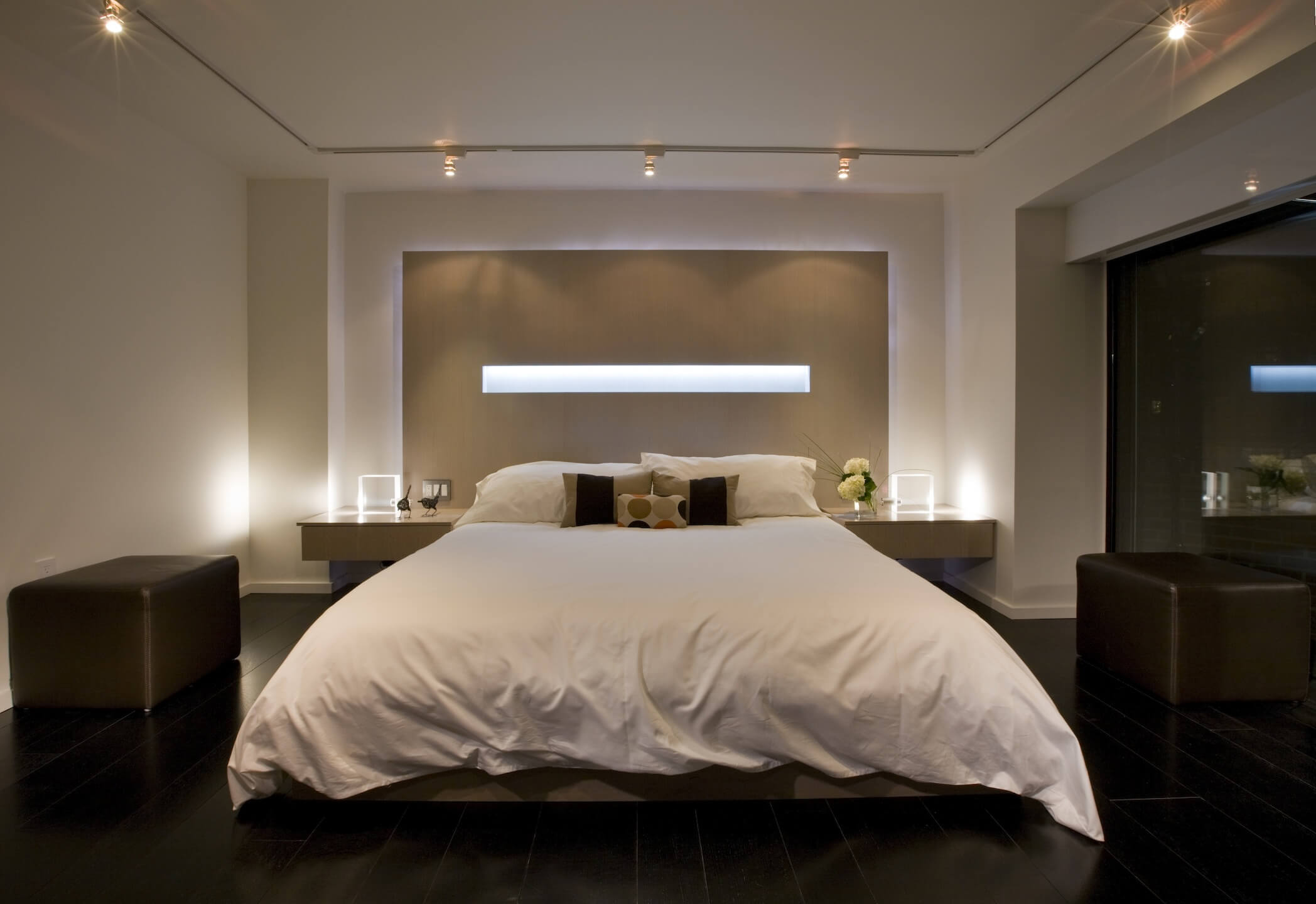 Head-on view of master bedroom, showcasing white-covered bed in front of monolithic wall detail containing horizontal light strip. Large dark leather ottomans stand on each side.