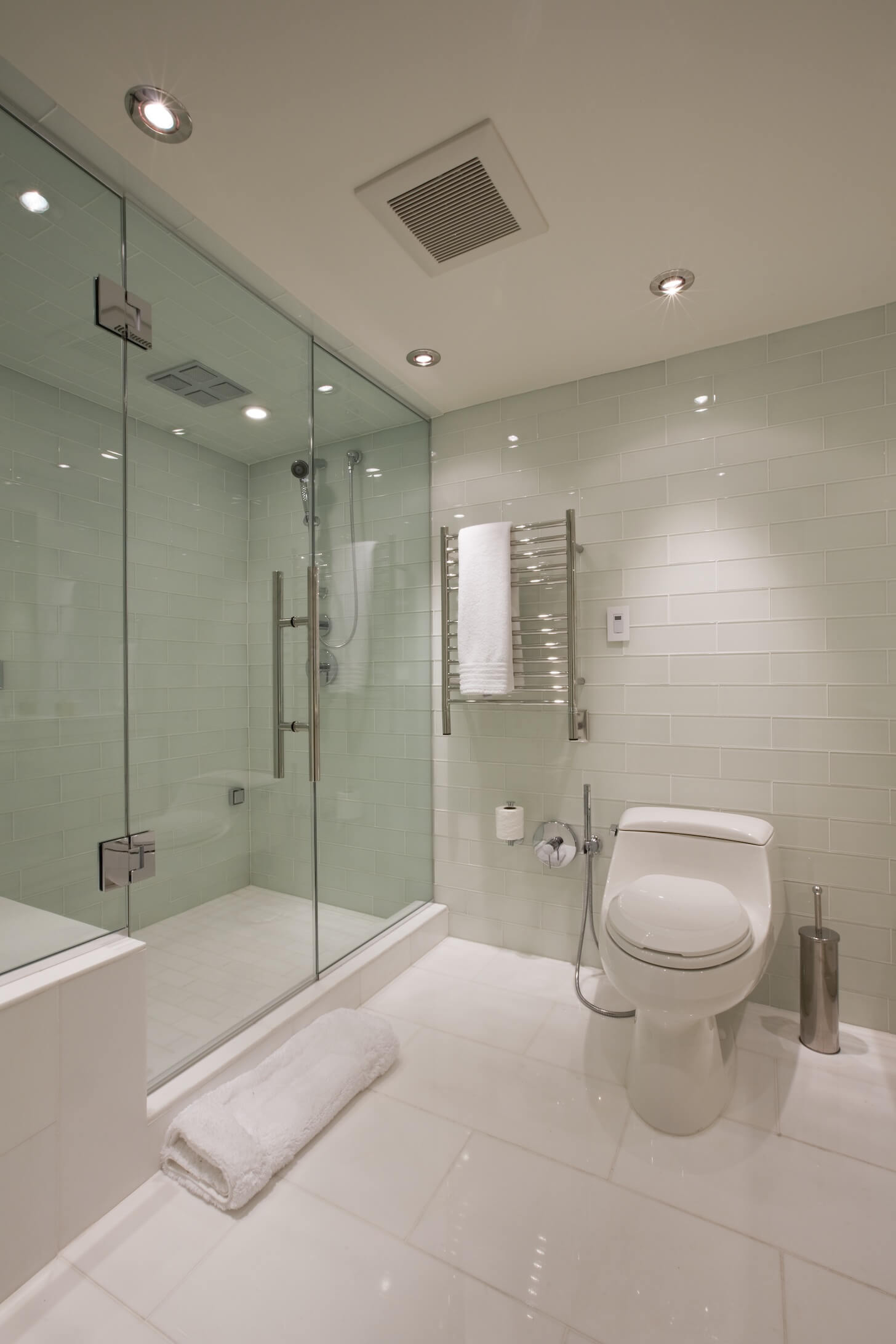 Bathroom features large white floor tiling and smaller brick-style wall surface, with large glass door shower on left.