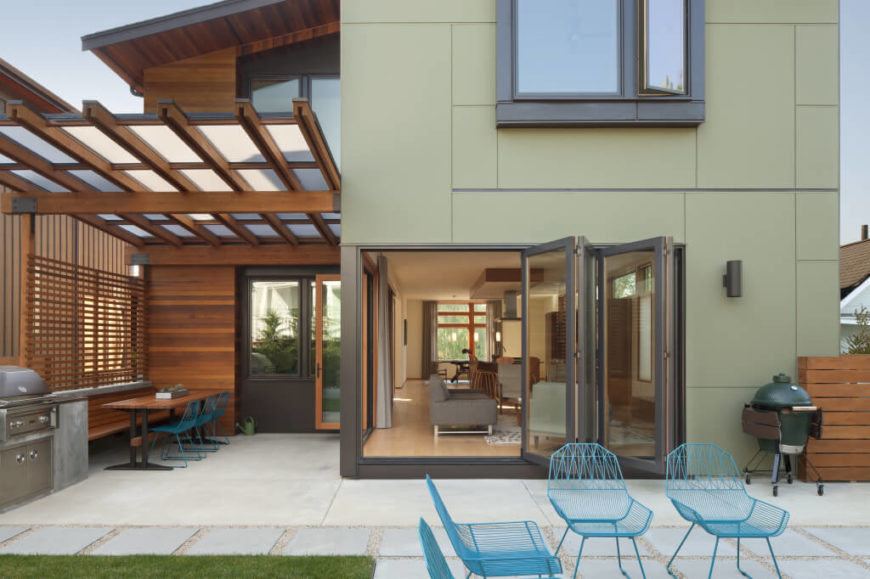 Rear patio, featuring natural wood outdoor dining area with built-in grill, stone patio flooring, blue metal chairs and upper doorway overlooking.