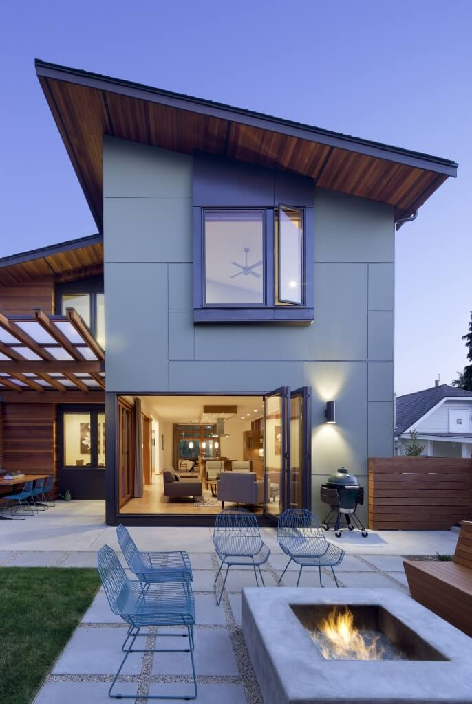 Nighttime, pulled-back view of rear yard, highlighting concrete fire pit and folding open back living room door design, leaving home completely open in the rear.