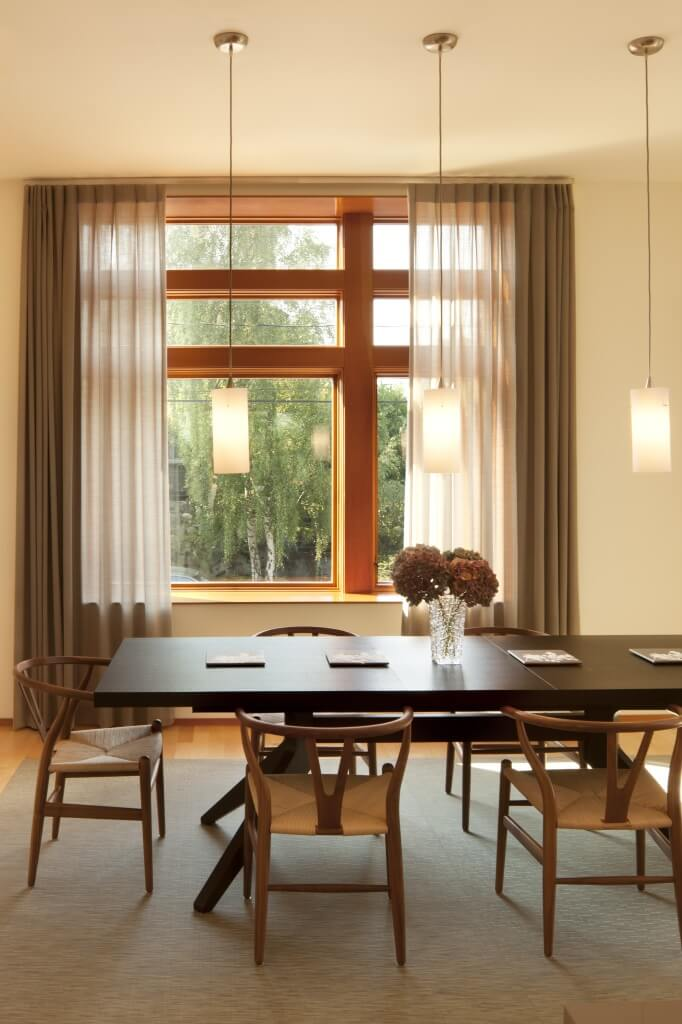 Close view of dining area, with dark wood table pairing with lighter natural wood chairs over a beige rug. Yet another ceiling height window offers natural light, behind hung minimal chandeliers.