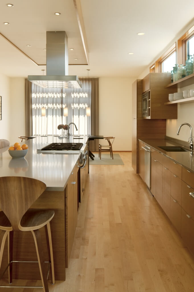 View of kitchen space, with yet another tone of natural wood on all minimalist cabinetry and carved wood stools. Slate countertops and second sick on island with built-in range complete the space. Dining room at far end.