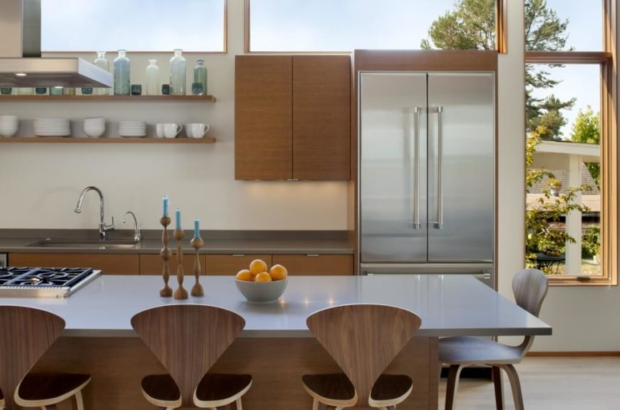 Side view of kitchen area, highlighting grey tone countertop and nearly matching aluminum refrigerator sitting below huge windows completing the surrounding open view.