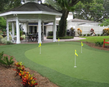 Luxury private putting green next to gazebo in large backyard