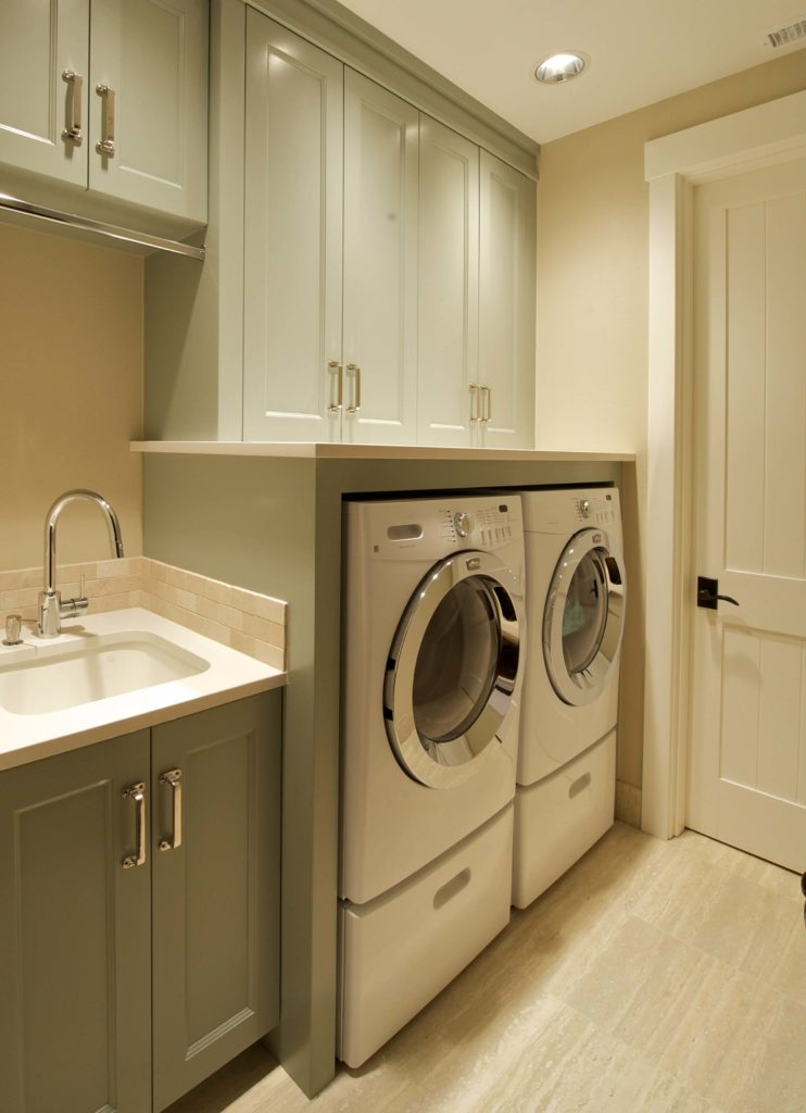 Laundry room extends off bathroom featuring under-shelving space for washing machine and dryer next to dedicated laundry sink. Light green cupboards pair with beige flooring and wall paint.