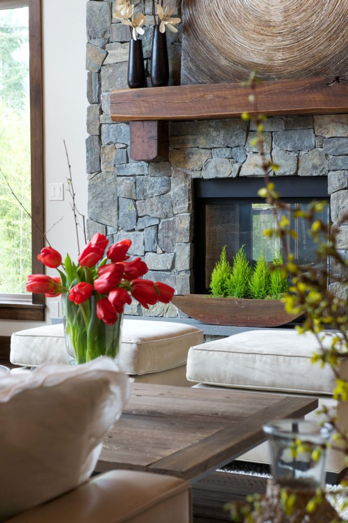 View over the furniture of the fireplace and surrounding space. Light toned furniture and wall paint contrasts with dark stone fireplace surround and wood coffee table. Vegetation adds burst of color.