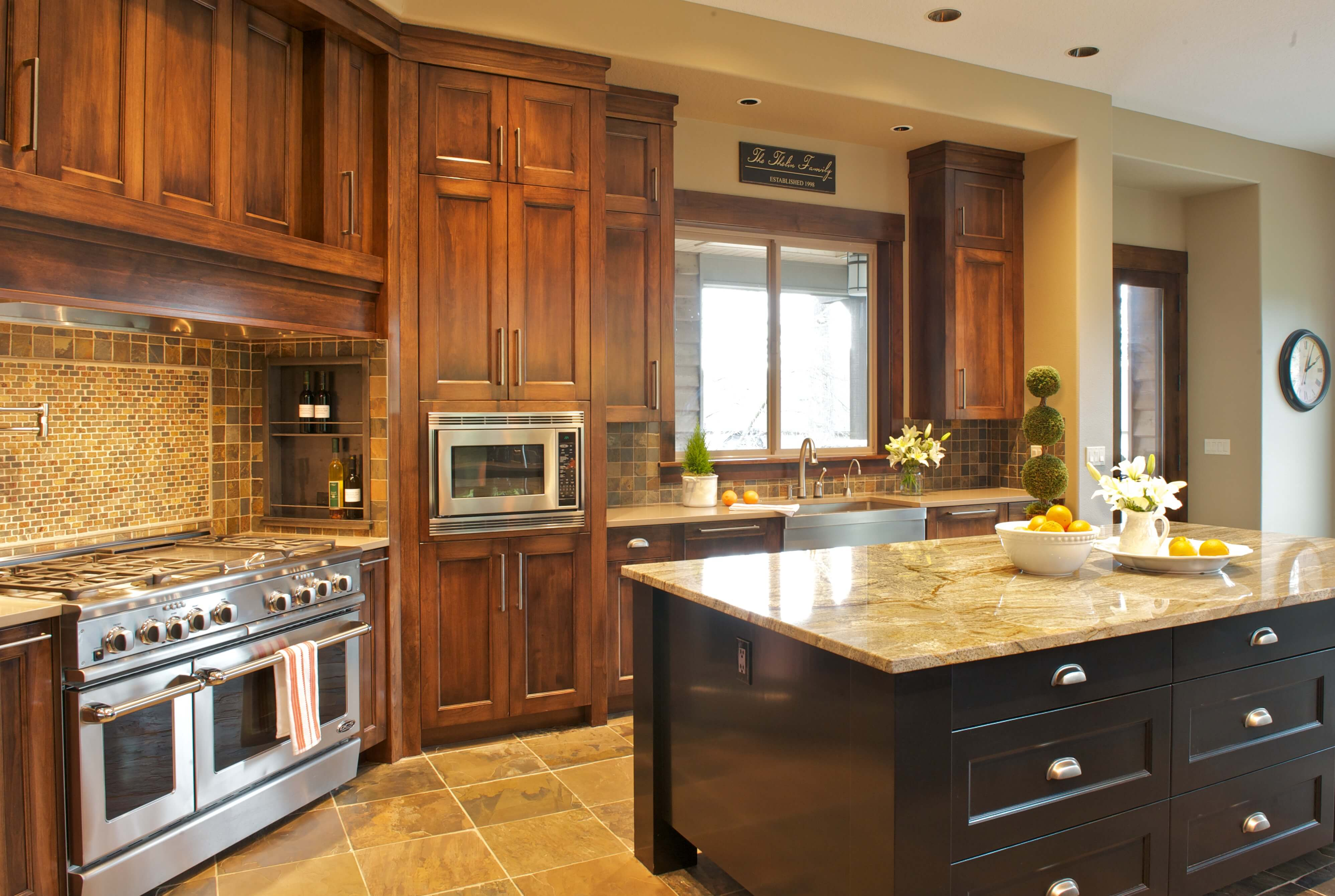 Kitchen is centered around large black island with marble countertop. Red wood cabinetry stands over earth tone tile flooring with patterned tile backsplash for warm look.