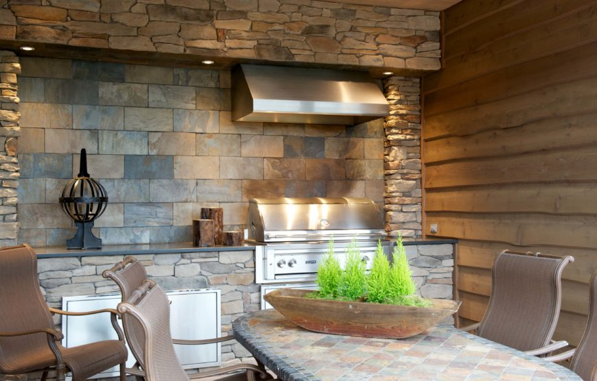 Here is the outdoor dining area with grill built into stone wall with slate countertops.