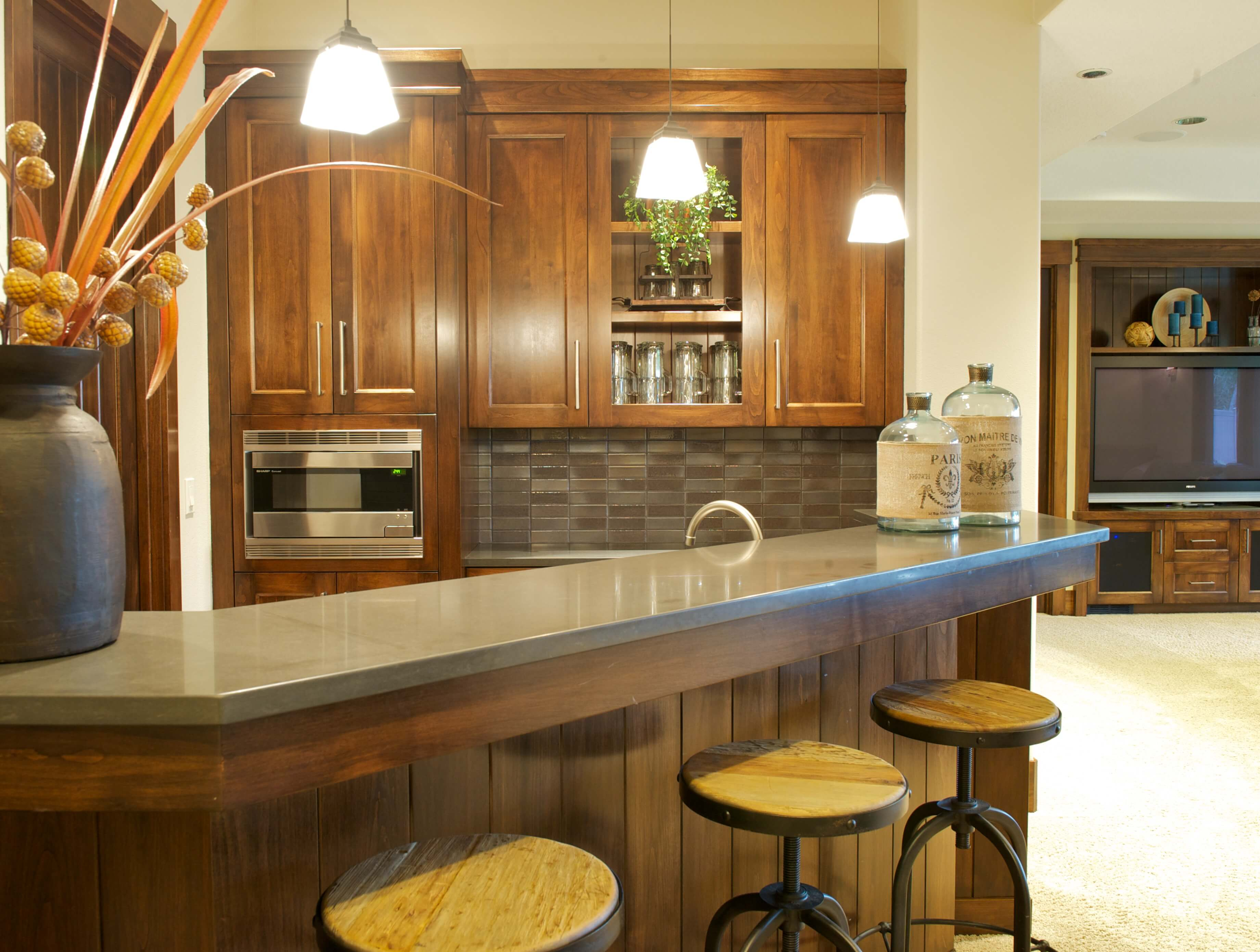 Unique bar area separate from kitchen features matching wood and metal bar stools and grey tile backsplash with matching countertop and exposed glassware storage.