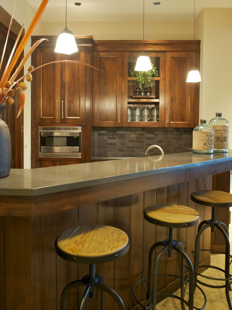 Fuller view of bar area, highlighting dark wood paneling and angled row of chandeliers.