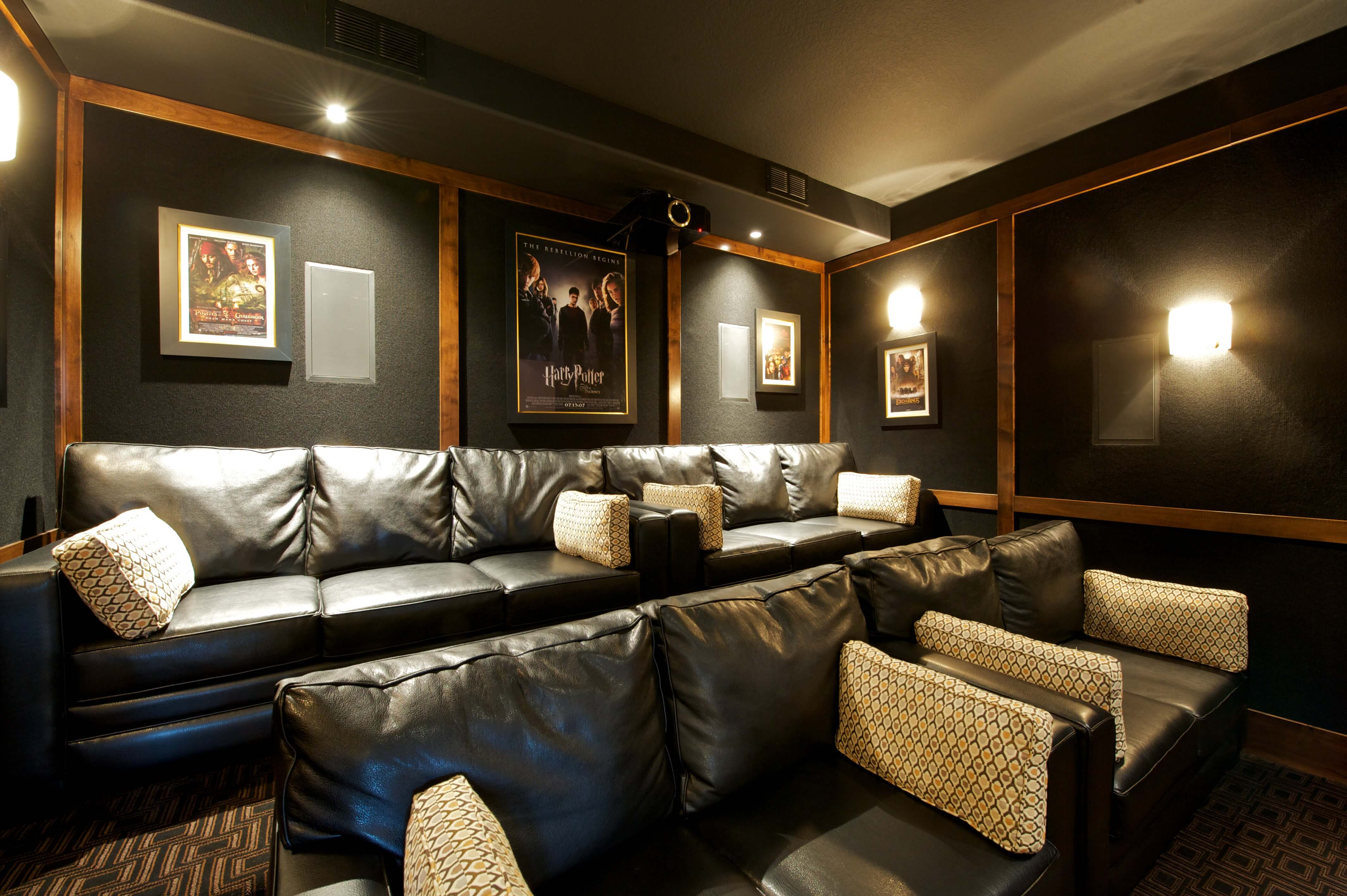 Dedicated cinema room features tiered rows of black leather couches, with black walls accented by natural wood moldings.