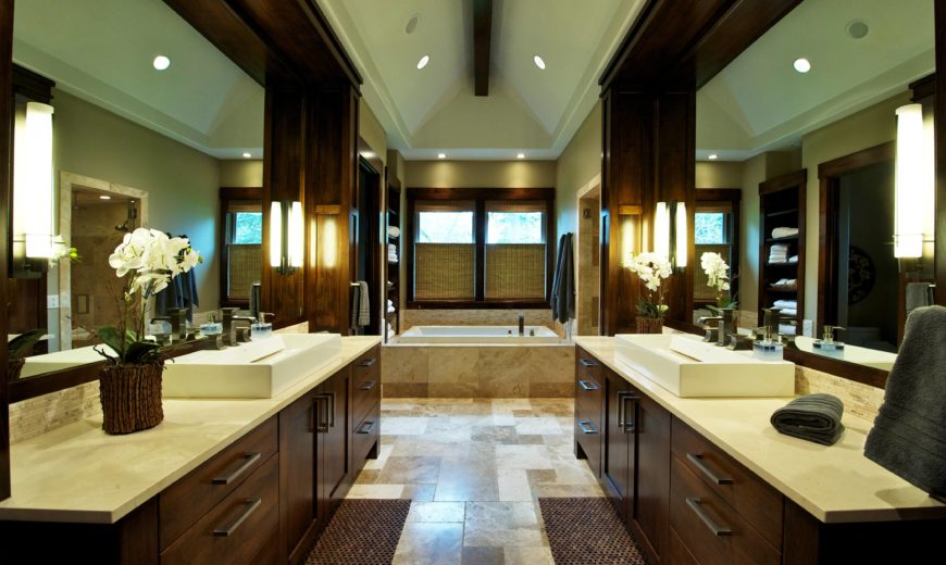 The master bath is replete with twin rich, dark wood cabinetry and mirror surrounds over earth tone tile flooring with large bath in background. Single exposed beam runs down length of vaulted ceiling.