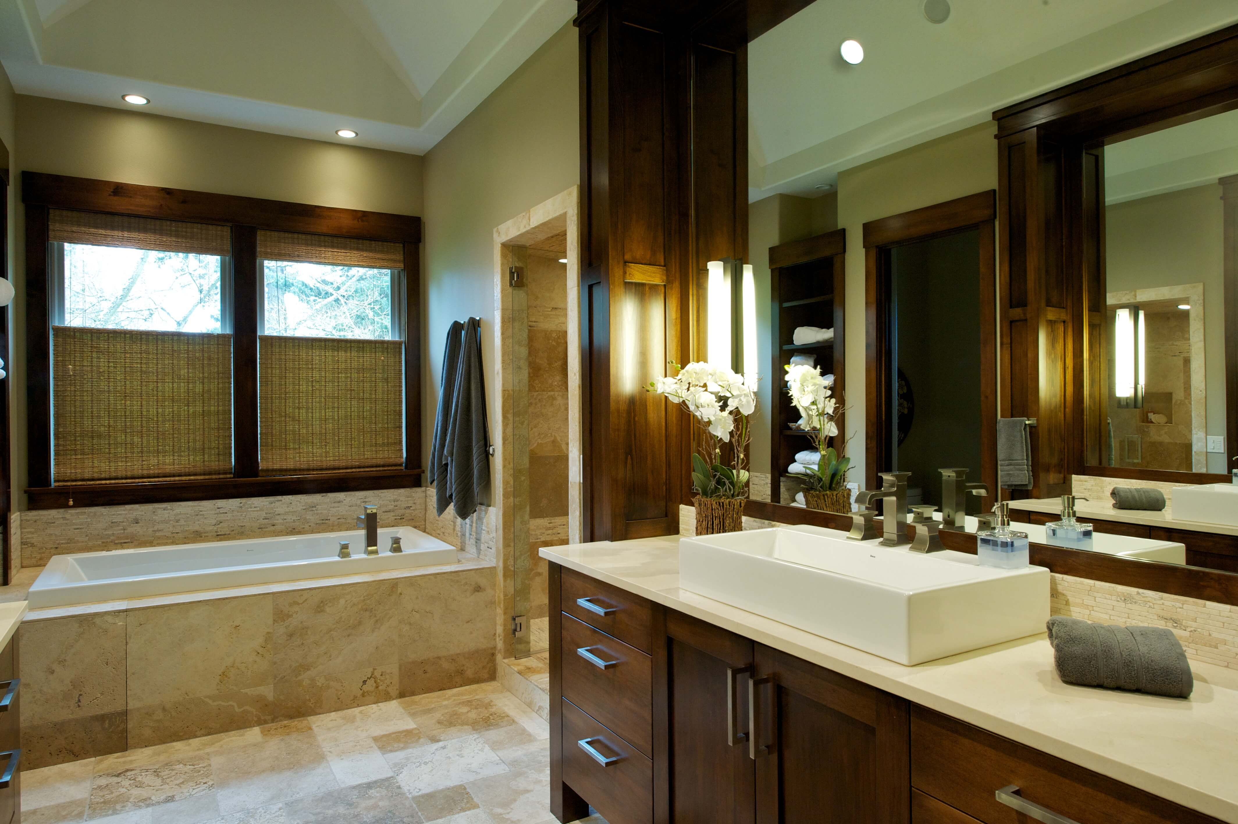 Closer view of bathroom counter space with rectangular vessel sink and small tile backsplash. Large tub surround is seen on left.