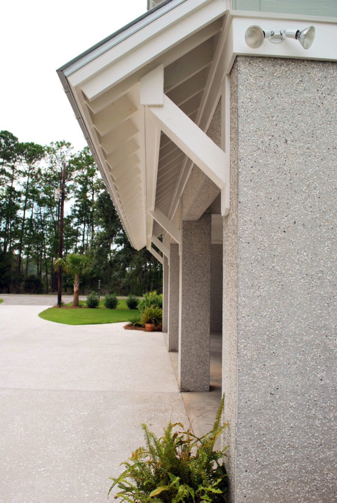 Close profile view of garage entrance. Concrete pillars seamlessly part of structure.