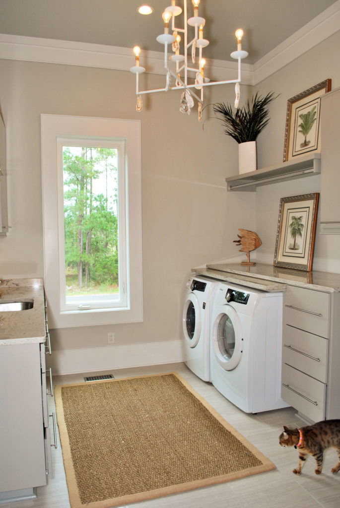 Wide view of laundry room with light brown rug over slate floor, with shelving built over appliances and chandelier hanging over large window.