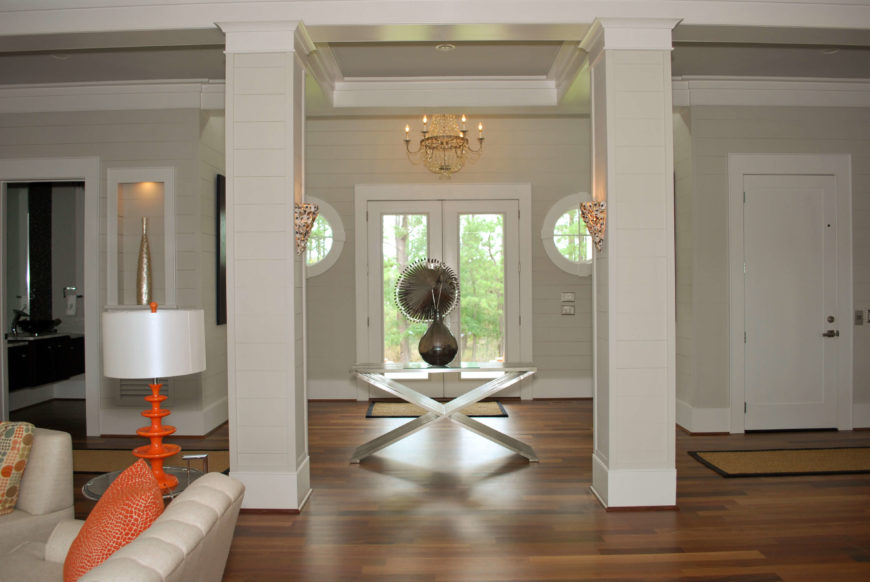 Front entrance interior, seen between two main pillars. Natural hardwood flooring, delicate wall sconces, chandelier, and unique decorations abound.