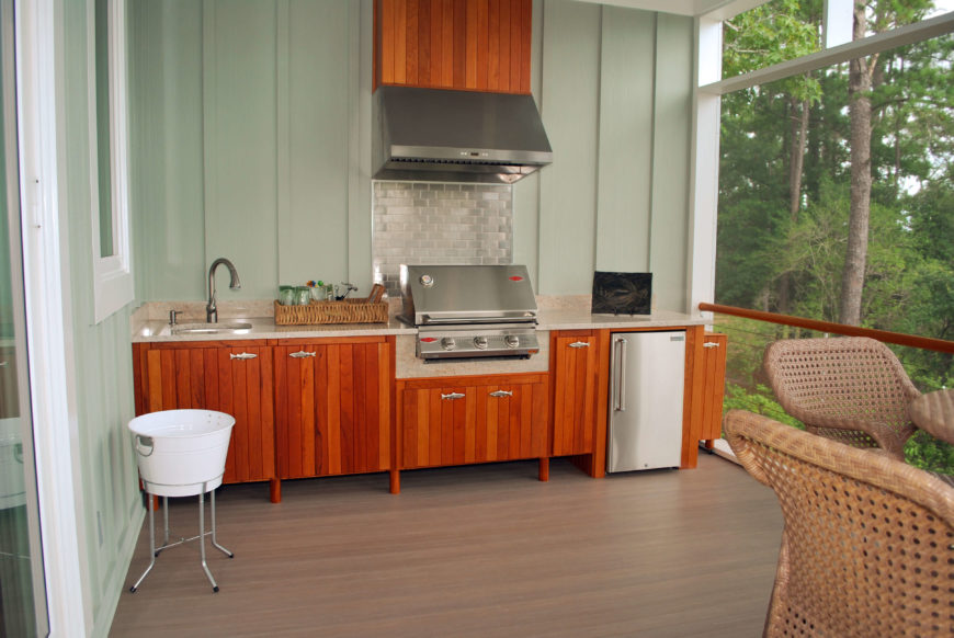 Close view of outdoor kitchenette, complete with mini refrigerator and built-in grill.