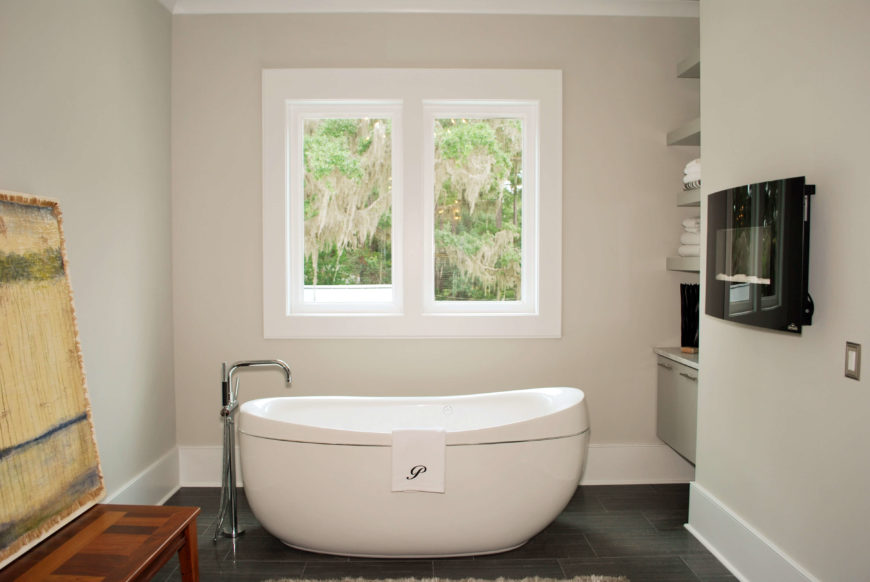 Standalone pedestal tub, dark tile flooring, and small wall mounted fireplace feature in bathroom.