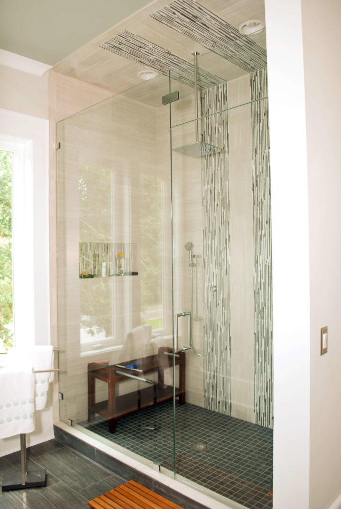 Master bath features glass door shower with patterned tile accents and wood seating.