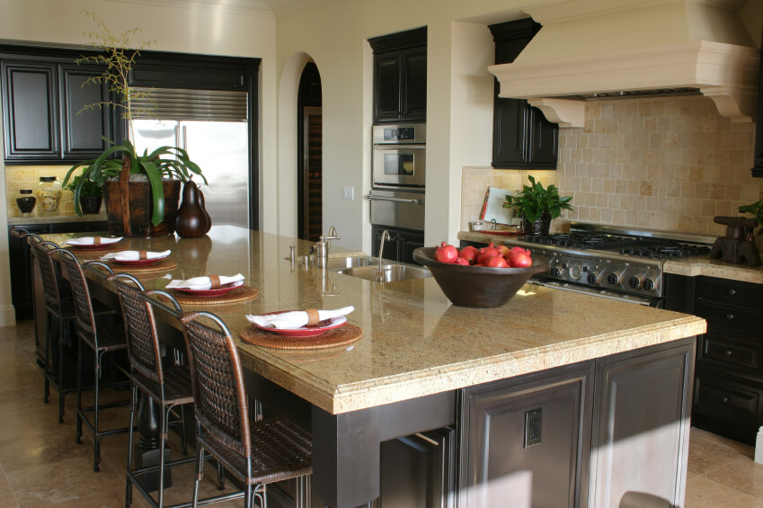 Expansive island matches dark wood and light marble countertop theme of kitchen, with lengthy dining seating and secondary sink built-in.